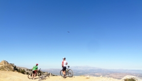 mountain bikers watch a vulture flying above them
