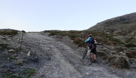 cyclists passes a fence at Monodendri mountain Crete