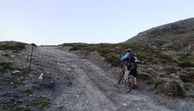 cyclists passes a fence at Monodendri mountain Crete