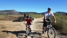 dad, son on their mountain bikes and local farmers with agricaltural old machine