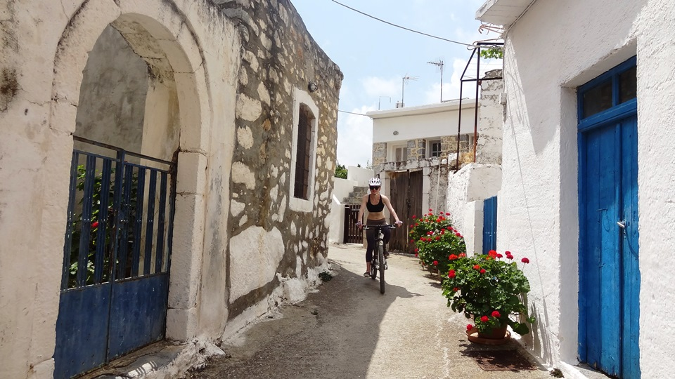 a lady rides her mountain bike through the narrow roads of mochos village