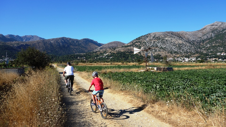 a father with his kid ride their mountain bikes at Lasithi plateau