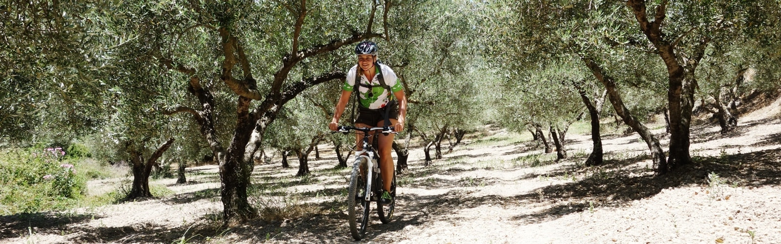 cycling-lady-in-a-an-garden-with-olive-trees-at-deliana-canyon-crete-min