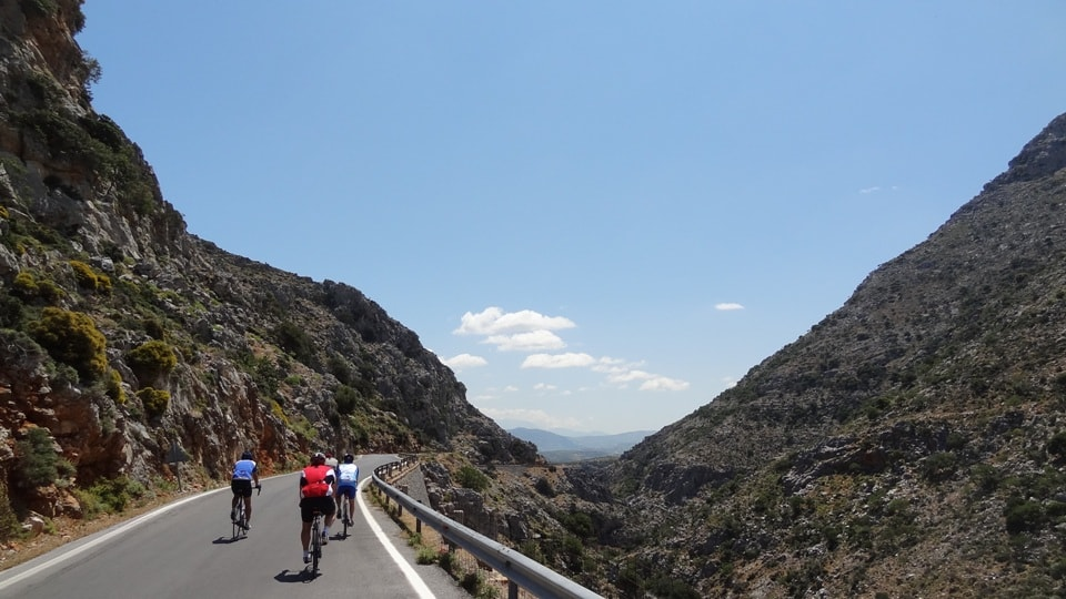 three road cyclists pass through the goniano canyon of Crete