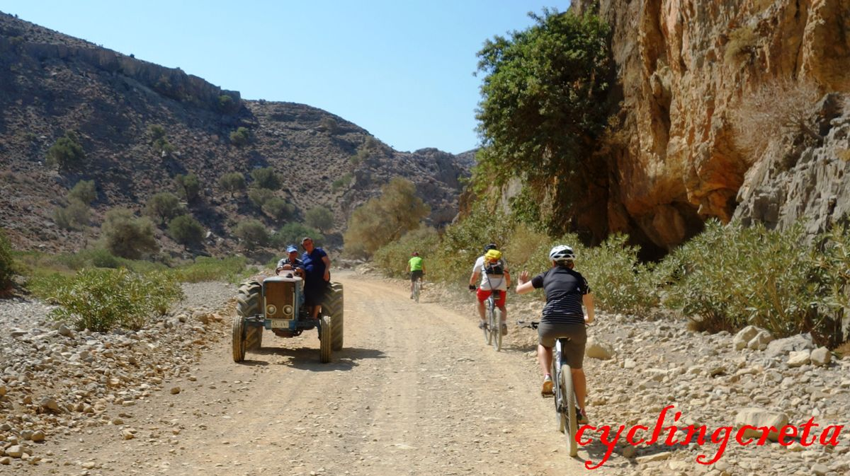 farmers couple on tractor at tripitis anyon asterousia mountains and cyclists