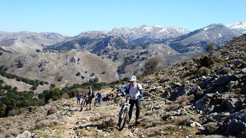 pushing the bikes on a mountain path crete
