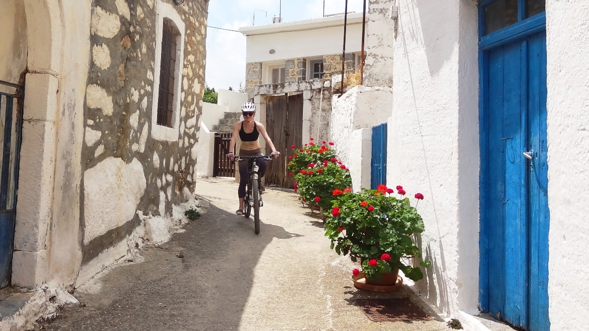 lady cyclists rides in the small street of mochos village crete