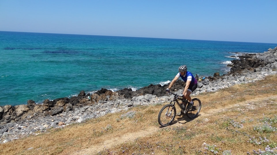 cyclist rides his bike next to the sea malia bike region image